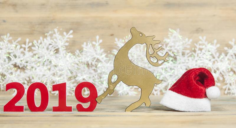 Funny christmas card with reindeer wearing a santa hat for a greetings on a wooden background. Christmas reindeer with santa hat in festive setting stock images