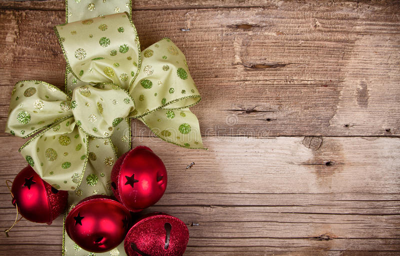 Christmas ribbon and ornaments on a wooden background. Green Christmas ribbon with red Chirstmas Ornaments on a rustic wooden background royalty free stock photography