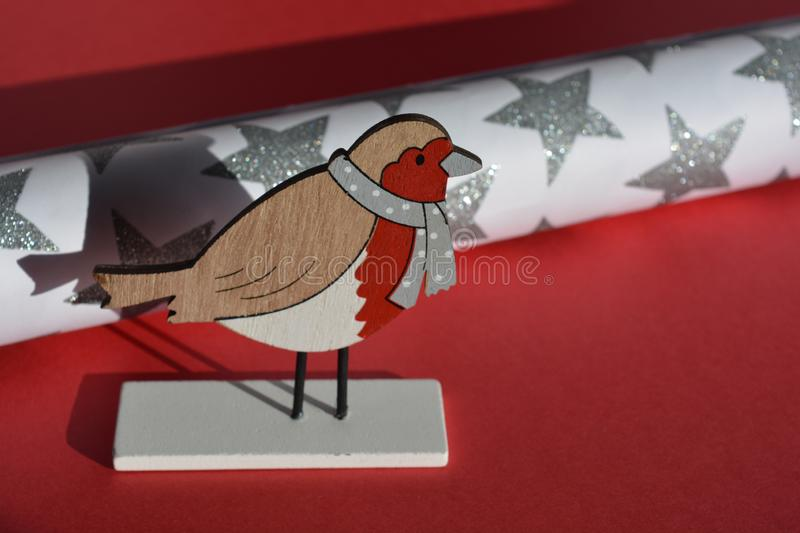 Christmas robin decoration with copy space. It`s Christmas. Time to start wrapping presents. Cute wooden robin redbreast decoration and a roll of silver glitter royalty free stock photo