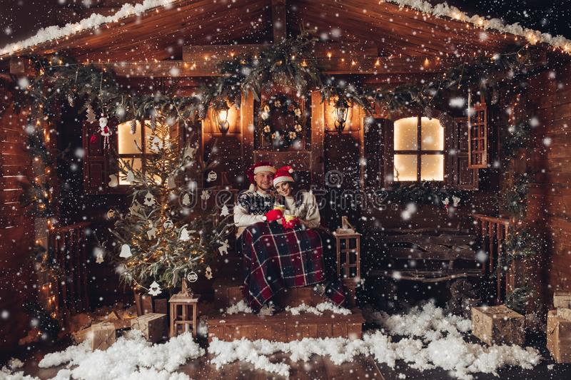 Christmas romance in Santa Claus hats beautiful house New Year`s atmosphere royalty free stock photo