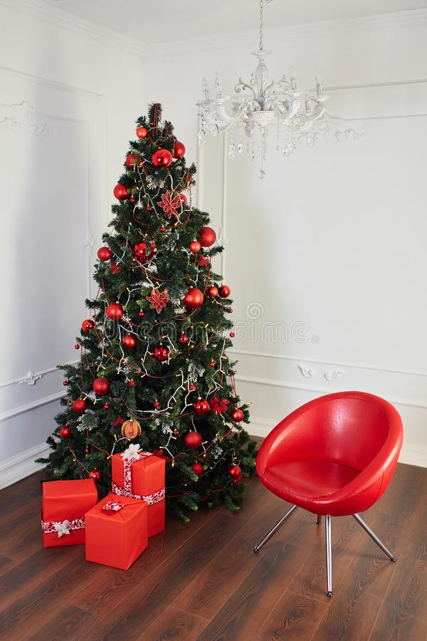 Christmas Room Interior, Green Xmas Tree, Present Gifts. Christmas tree with gifts and a red chair royalty free stock photo