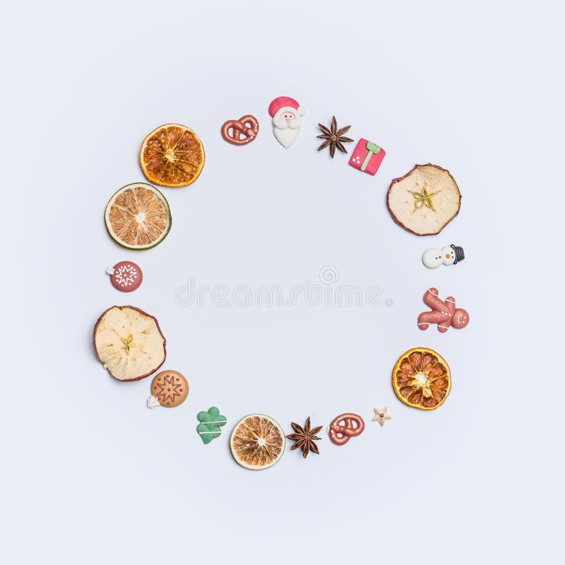 Christmas round circle fame or wreath made with dried fruits and anise stars and marzipan Christmas decor figures. Santa, tree, ginger man, snowman and balls stock photos