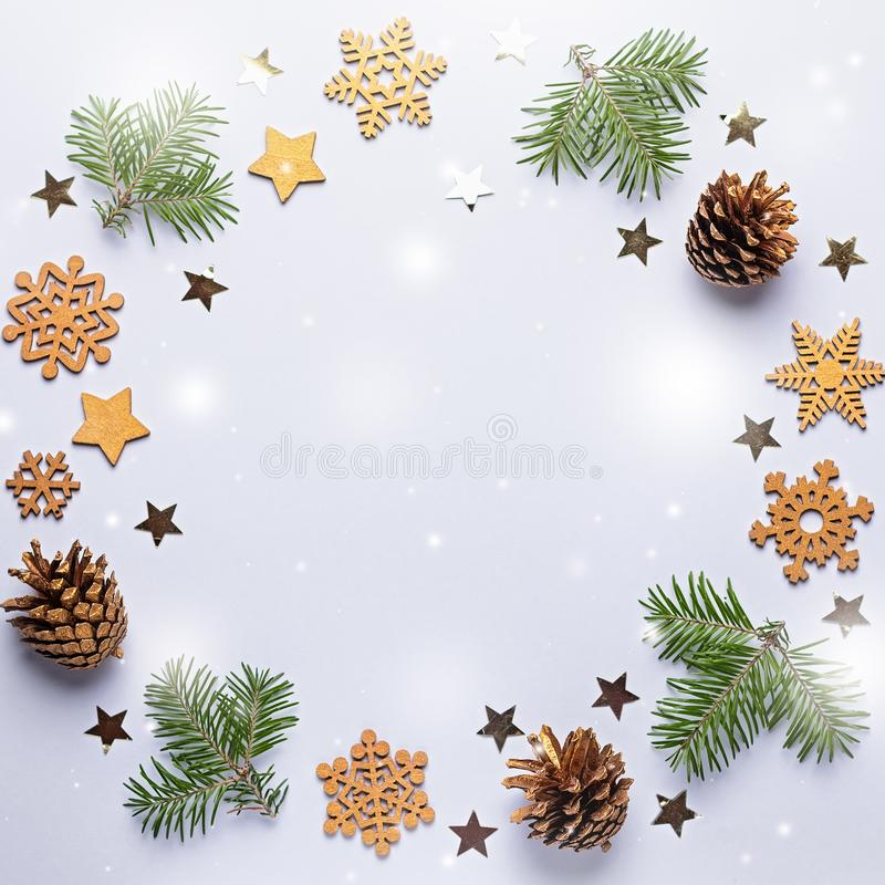 Christmas round frame with golden ornaments, painted snowflakes, pine cones, confetti on grey background, copy space. Minimalistic christmas wreath stock photography