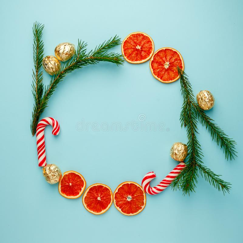 Christmas round frame made of natural pine branches, traditional xmas sweetness candy cane and candied fruit citrus on blue backgr royalty free stock image