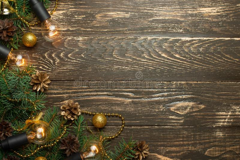 Christmas rustic background - old wooden board with backlight and branches of a Christmas tree and shyshkami and a free text space. Christmas rustic background royalty free stock image