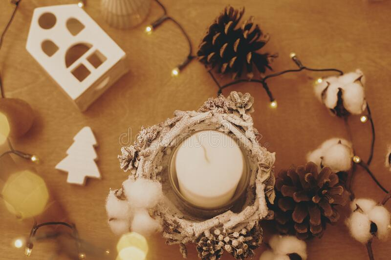 Christmas rustic candle, pine cones, wooden tree, toy house and  festive lights on wood. Flat lay. Rustic christmas candle decor royalty free stock photo