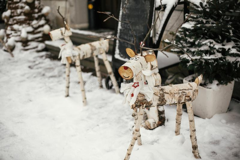 Christmas rustic street decor. Stylish christmas wooden reindeer and snowman at rustic christmas tree at store front at holiday. Market in snowy city street royalty free stock images