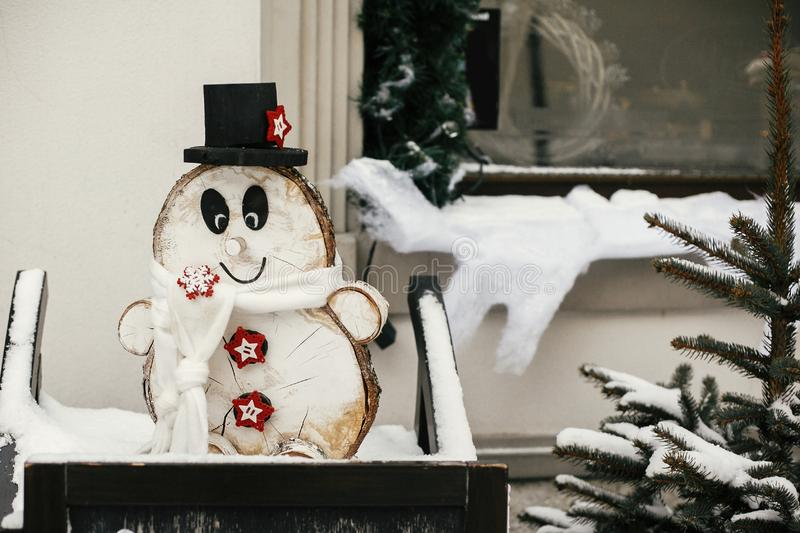 Christmas rustic street decor. Stylish christmas wooden snowman at rustic christmas tree at store front at holiday market in snowy stock photo