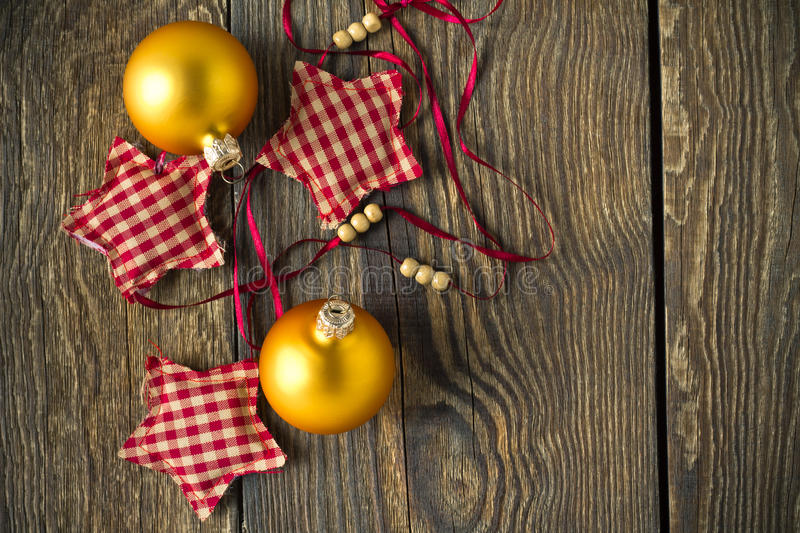 Christmas rustic wooden background with yellow balls. And decorative stars royalty free stock images