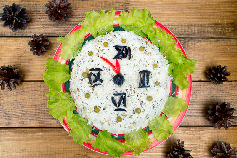 The Christmas salad rice olives greens peas - concept New year clock face, midnight, brown wooden background spruce royalty free stock photos
