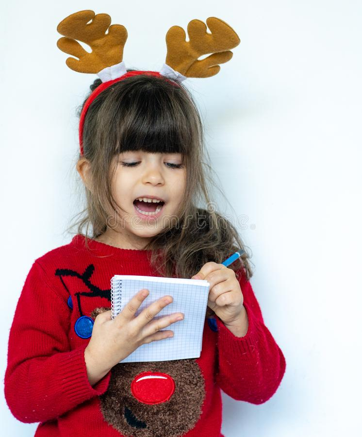 Christmas sale. Beautiful shocked kid holding pen and make a shopping list for New year sales. royalty free stock photo