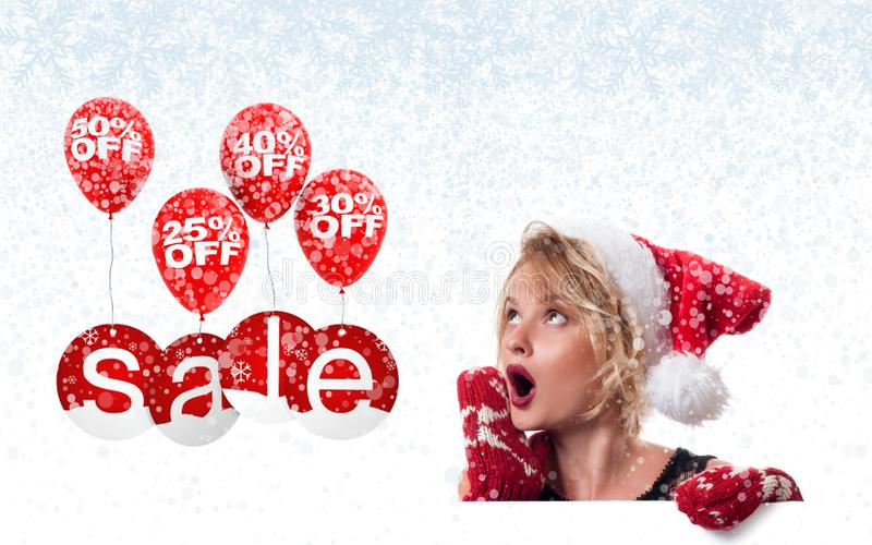 Christmas sale. Holiday. Beautiful womanin santa hat and mittens royalty free stock photo