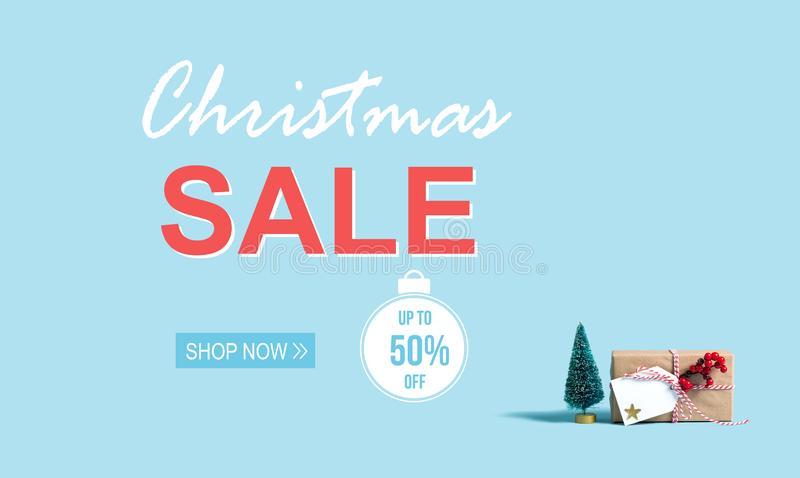Christmas sale message with Christmas gift box and tree. Christmas sale message with a Christmas gift box and toy tree royalty free stock images