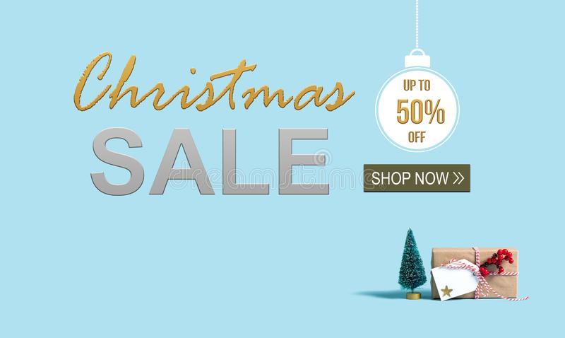 Christmas sale message with Christmas gift box and tree. Christmas sale message with a Christmas gift box and toy tree royalty free stock image