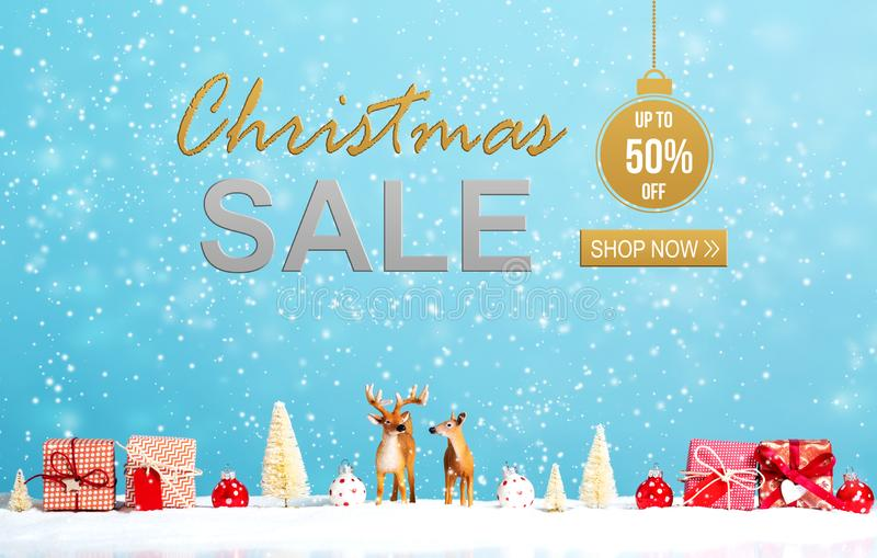 Christmas sale message with reindeer and Christmas gifts. In snowy day royalty free stock photos