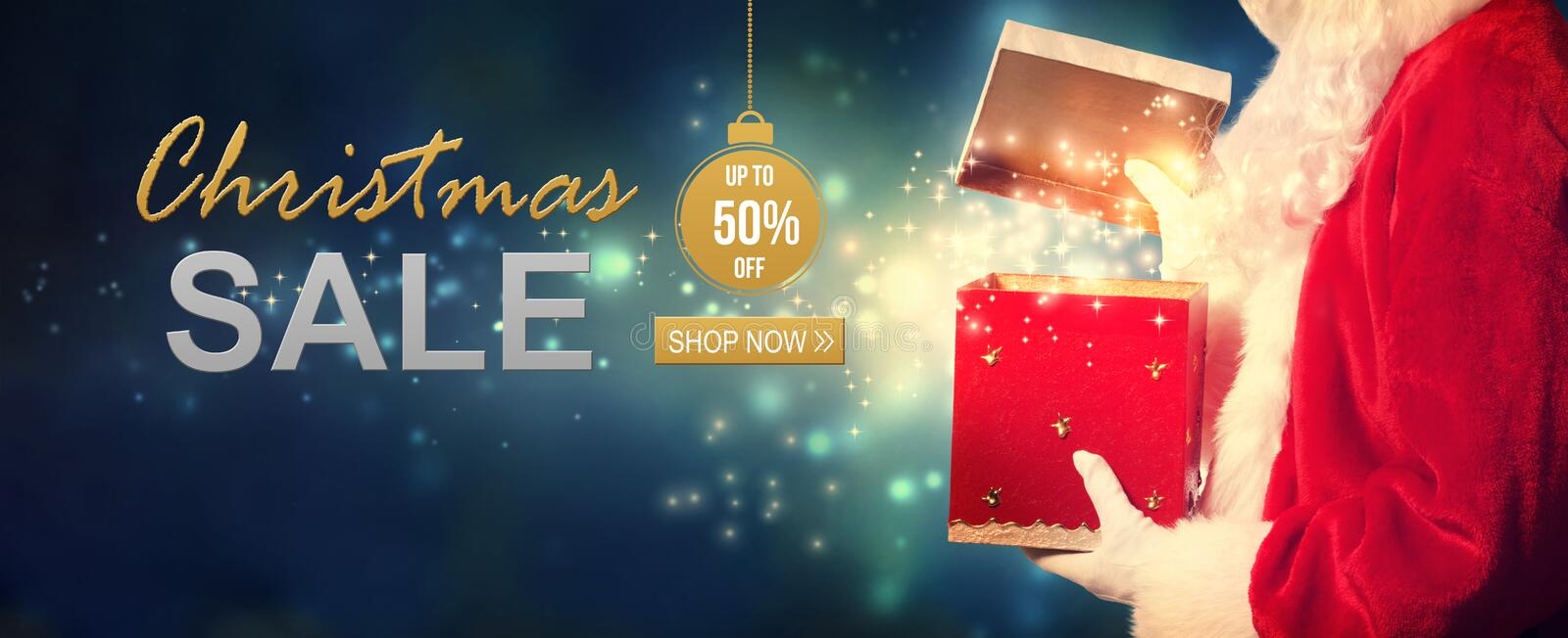Christmas sale message with Santa opening a gift box stock photos