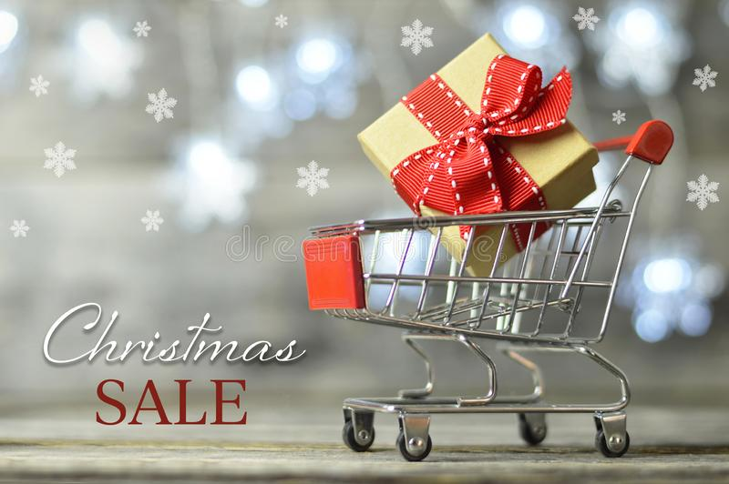 Christmas sale. Shopping cart and gift box. On wooden background stock photo