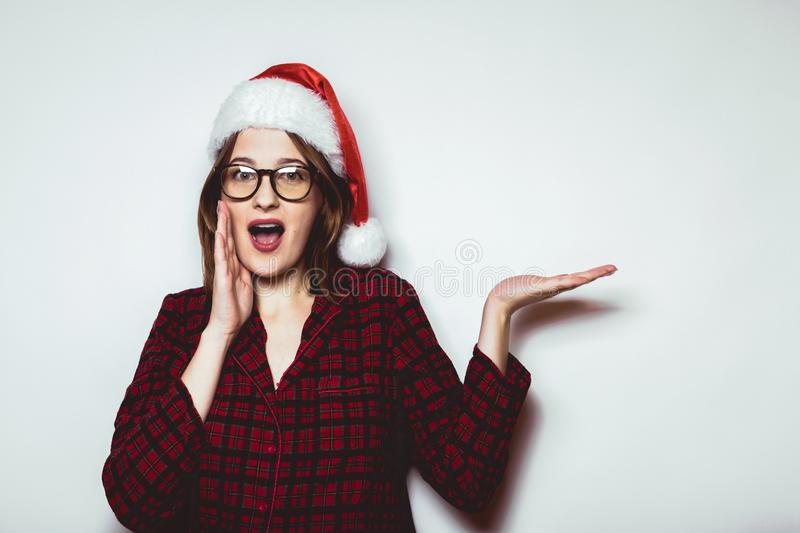 Christmas sale. Surprised young Santa Claus hat showing hand on. White background royalty free stock image