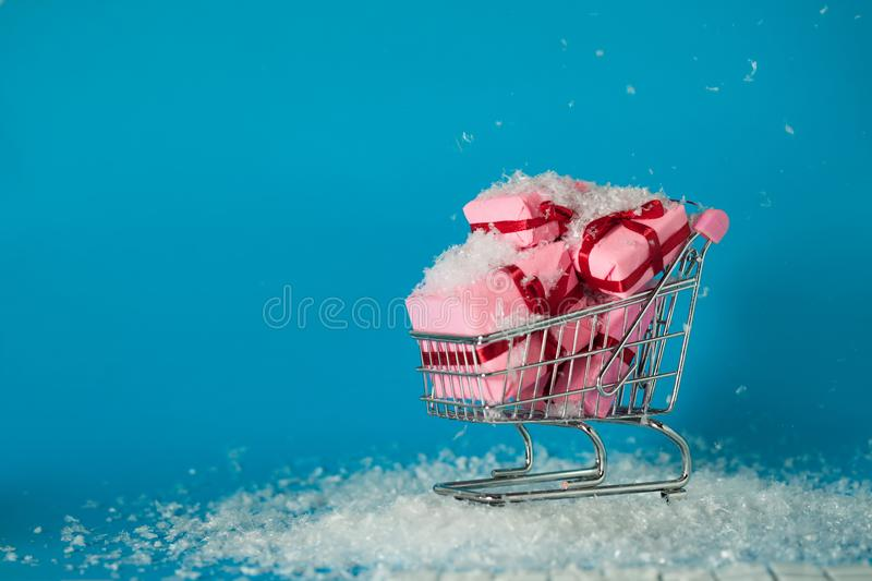 Christmas sales. Buying gifts for the new year, the concept. The shopping cart is full of gift boxes. Pink boxes on blue background royalty free stock image
