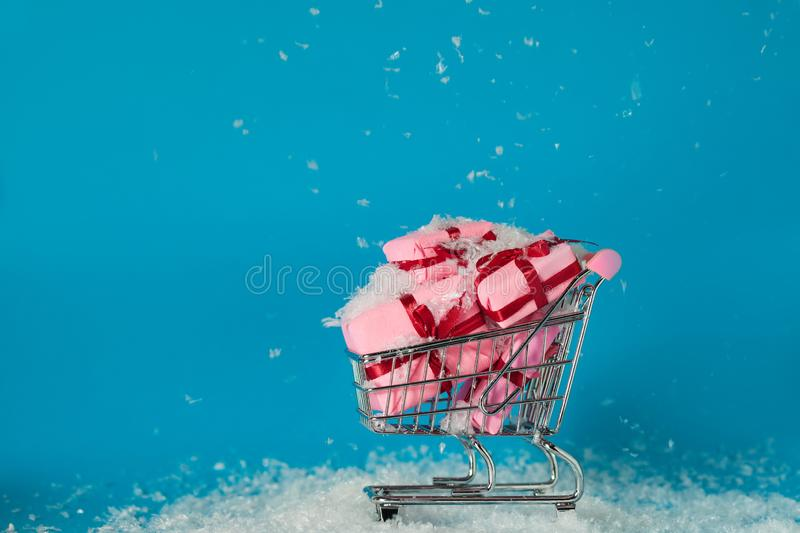 Christmas sales. Buying gifts for the new year, the concept. The shopping cart is full of gift boxes. Pink boxes on blue background stock photography
