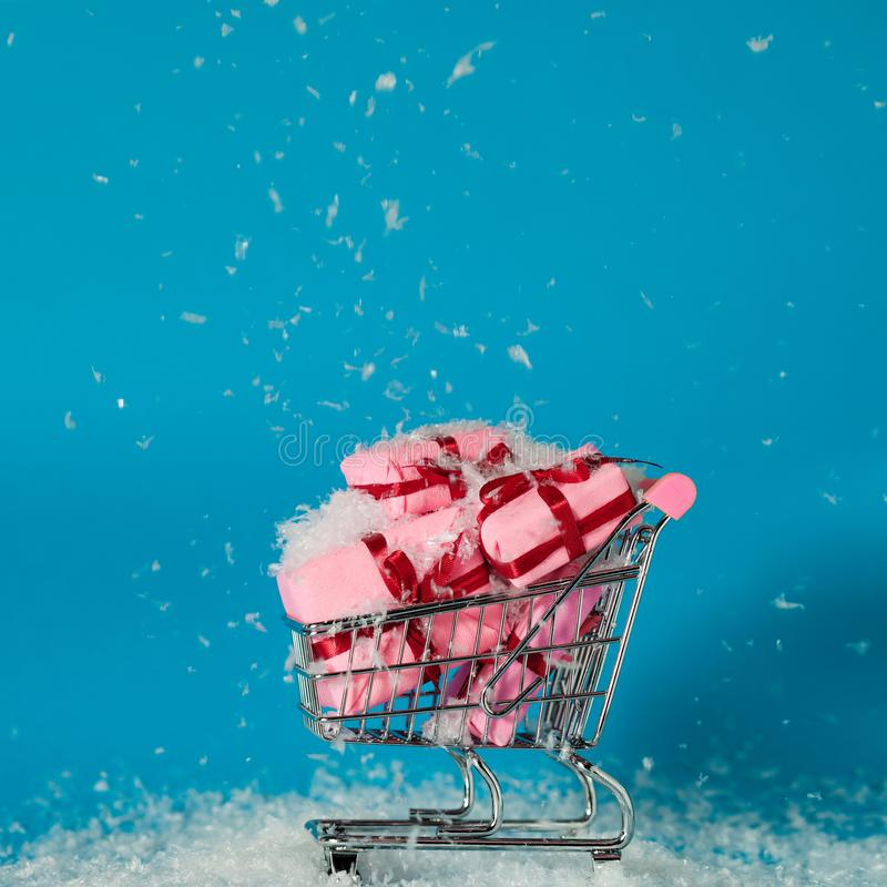 Christmas sales. Buying gifts for the new year, the concept. The shopping cart is full of gift boxes. Pink boxes on blue background royalty free stock photos