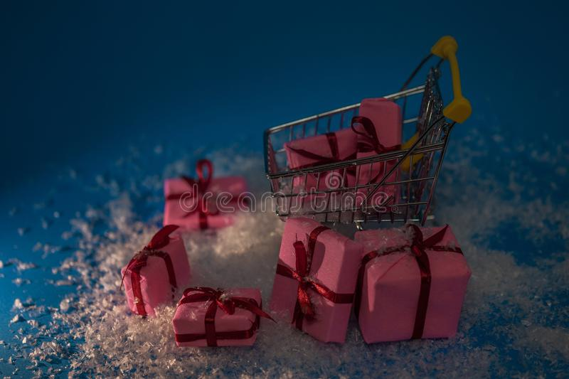 Christmas sales. Buying gifts for the new year, the concept. The shopping cart is full of gift boxes. Dark style royalty free stock image