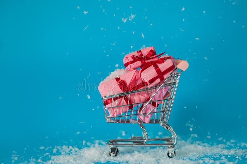 Christmas sales. Buying gifts for the new year, the concept. The shopping cart is full of gift boxes. Snowflakes fall on the boxes stock photos