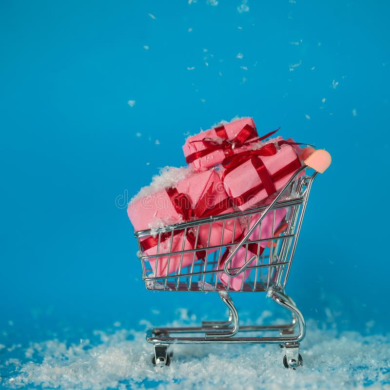 Christmas sales. Buying gifts for the new year, the concept. The shopping cart is full of gift boxes. Snowflakes fall on the purchase royalty free stock photos