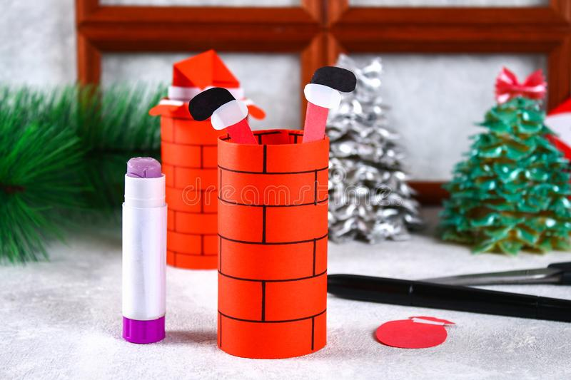 Christmas Santa Claus in chimney made from toilet paper hub, colored paper, marker, glue, fishing line and cotton pad. DIY toy on. The Christmas tree. Handmade royalty free stock image