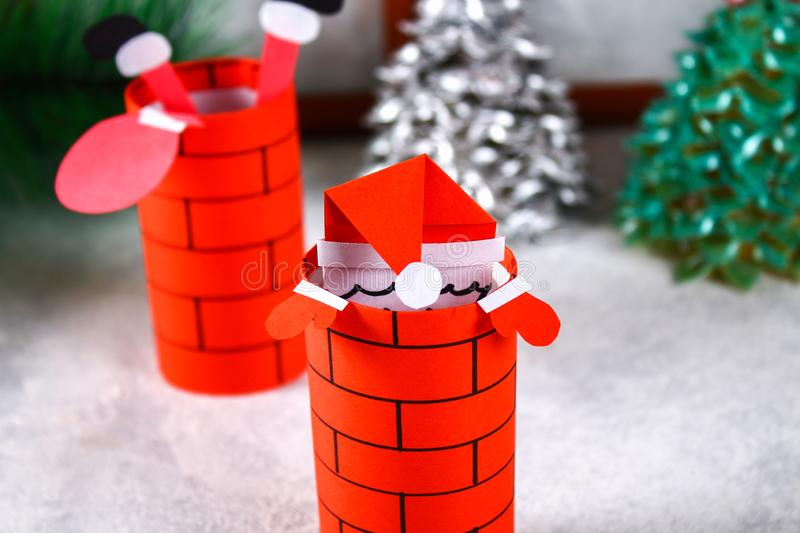 Christmas Santa Claus in chimney made from toilet paper hub, colored paper, marker, glue, fishing line and cotton pad. DIY toy on. The Christmas tree. Handmade stock photo
