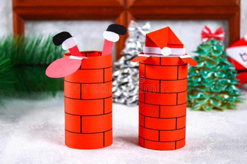 Christmas Santa Claus in chimney made from toilet paper hub, colored paper, marker, glue, fishing line and cotton pad. DIY toy on. The Christmas tree. Handmade stock images