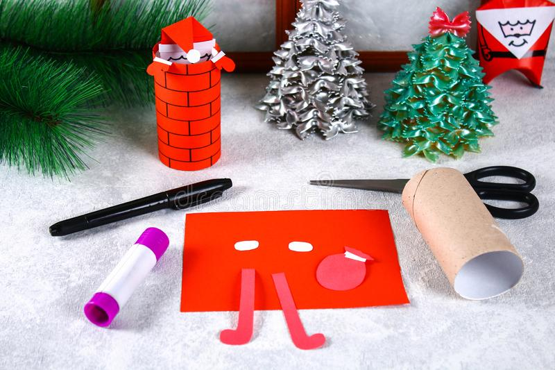 Christmas Santa Claus in chimney made from toilet paper hub, colored paper, marker, glue, fishing line and cotton pad. DIY toy on. The Christmas tree. Handmade royalty free stock images