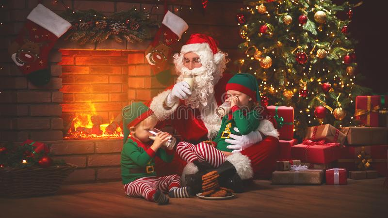 Christmas. Santa Claus with Elves Drink Milk and Eat Cookies royalty free stock image