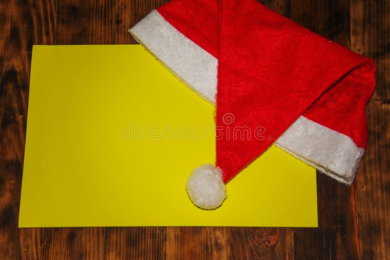 Christmas Santa Claus Hat On Wood Wall, Xmas Concept. Decoration Over Dark Grunge Wooden Background. Yellow Copyspace stock images