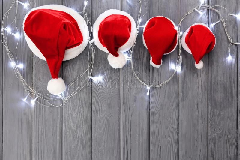 Christmas Santa Claus hats for family with garland. On wooden background royalty free stock images