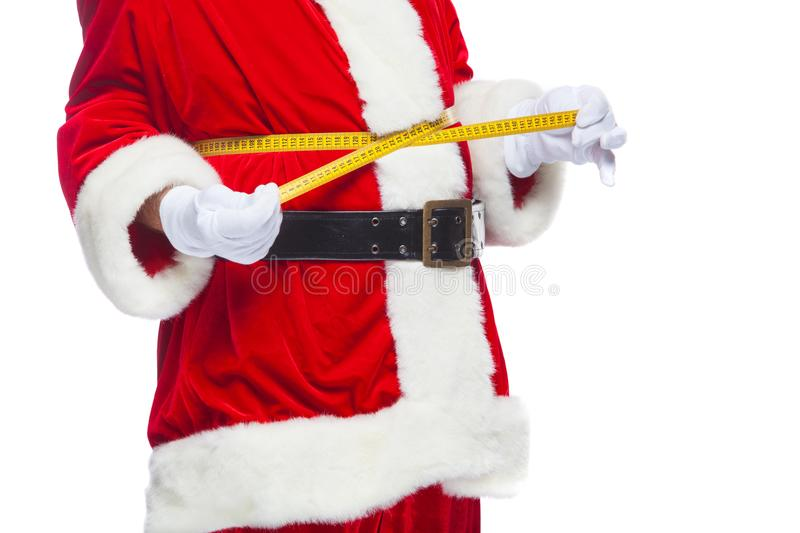 Christmas. Santa Claus is measuring waist with a tape. The concept of weight loss, healthy eating. Isolated on white royalty free stock photography