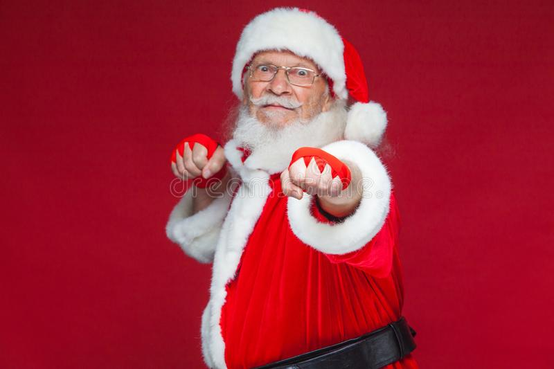 Christmas. Santa Claus with red bandages wound on his hands for boxing imitates kicks. Kickboxing, karate, boxing. On red background stock photo