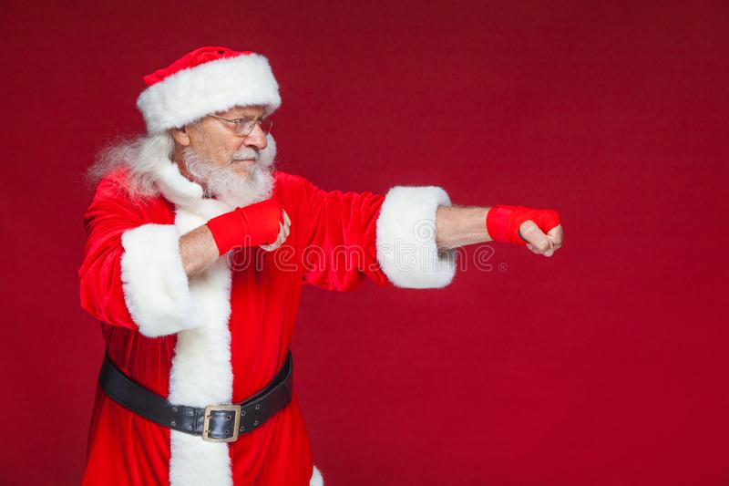 Christmas. Santa Claus with red bandages wound on his hands for boxing imitates kicks. Kickboxing, karate, boxing. Isolated on red background stock photos