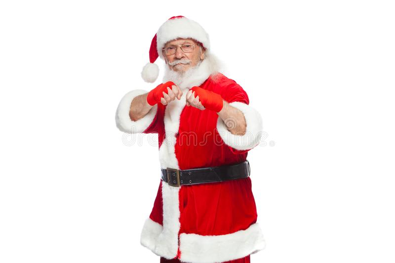 Christmas. Santa Claus with red bandages wound on his hands for boxing imitates kicks. Kickboxing, karate, boxing. Isolated on white background royalty free stock photos