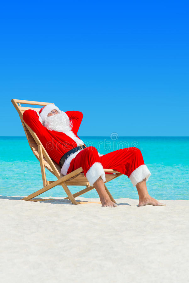 Christmas Santa Claus relax in deckchair at ocean sandy beach. Claus lounge in wooden deckchair at ocean tropical sandy beach - Year travel destinations vacation royalty free stock photos