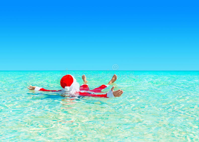 Christmas Santa Claus relax swimming in ocean turquoise transparent water. Santa Claus relax swimming in ocean turquoise transparent water. Merry Christmas and stock photos