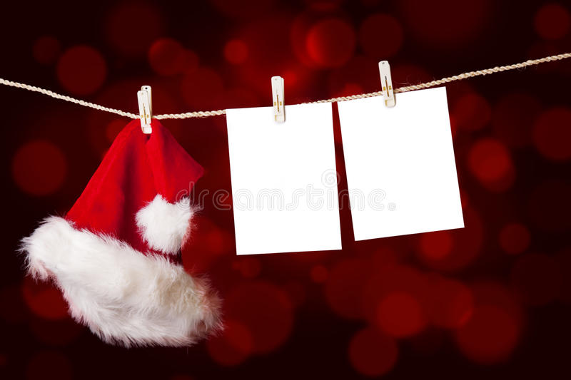 Christmas-santa-hat-and-notes-hanging-on-tree. A red christmas Santa hat is hanging on a string together with notes on defocused red lights stock image