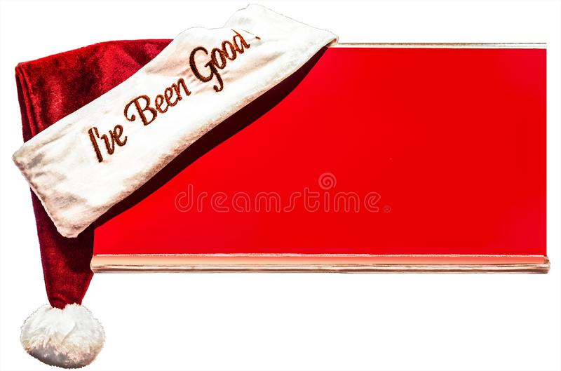 Christmas Santa hat with words - I`ve been good - perched on corner of red board with room for copy isolated on white background.  stock photos
