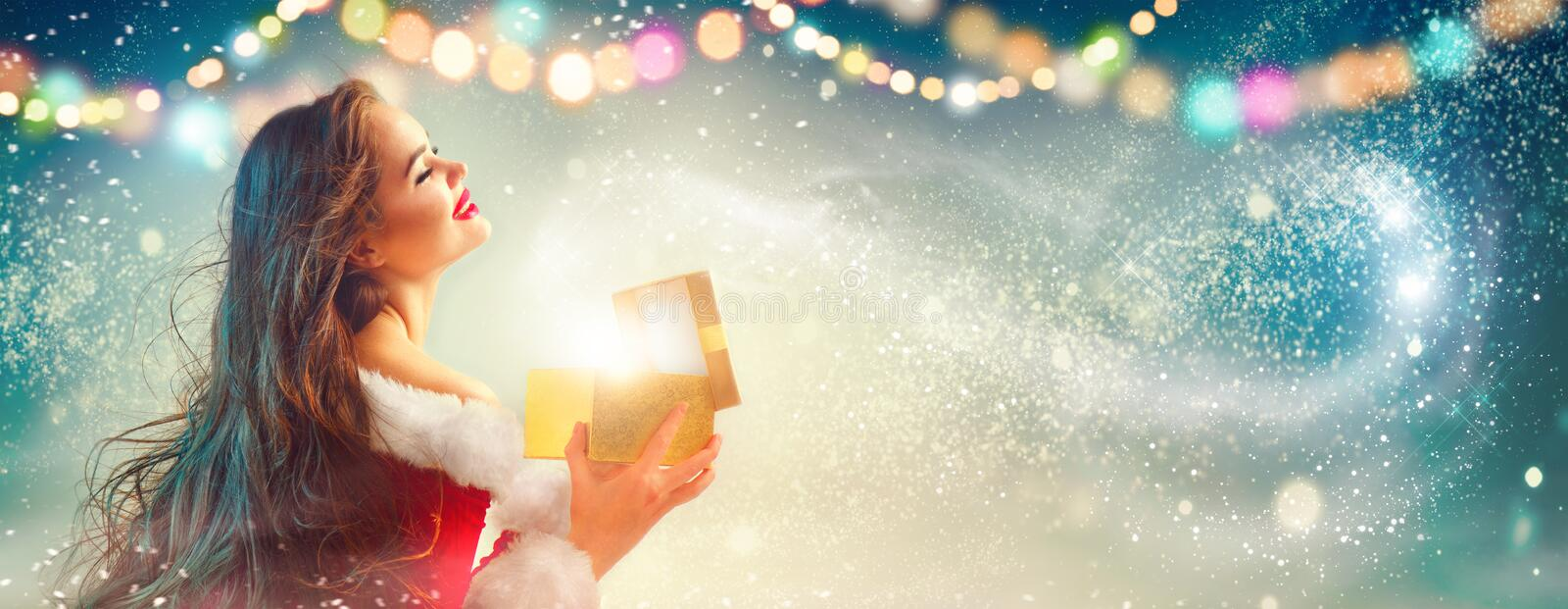 Christmas scene. Beauty brunette young woman in party costume opening gift box royalty free stock photo