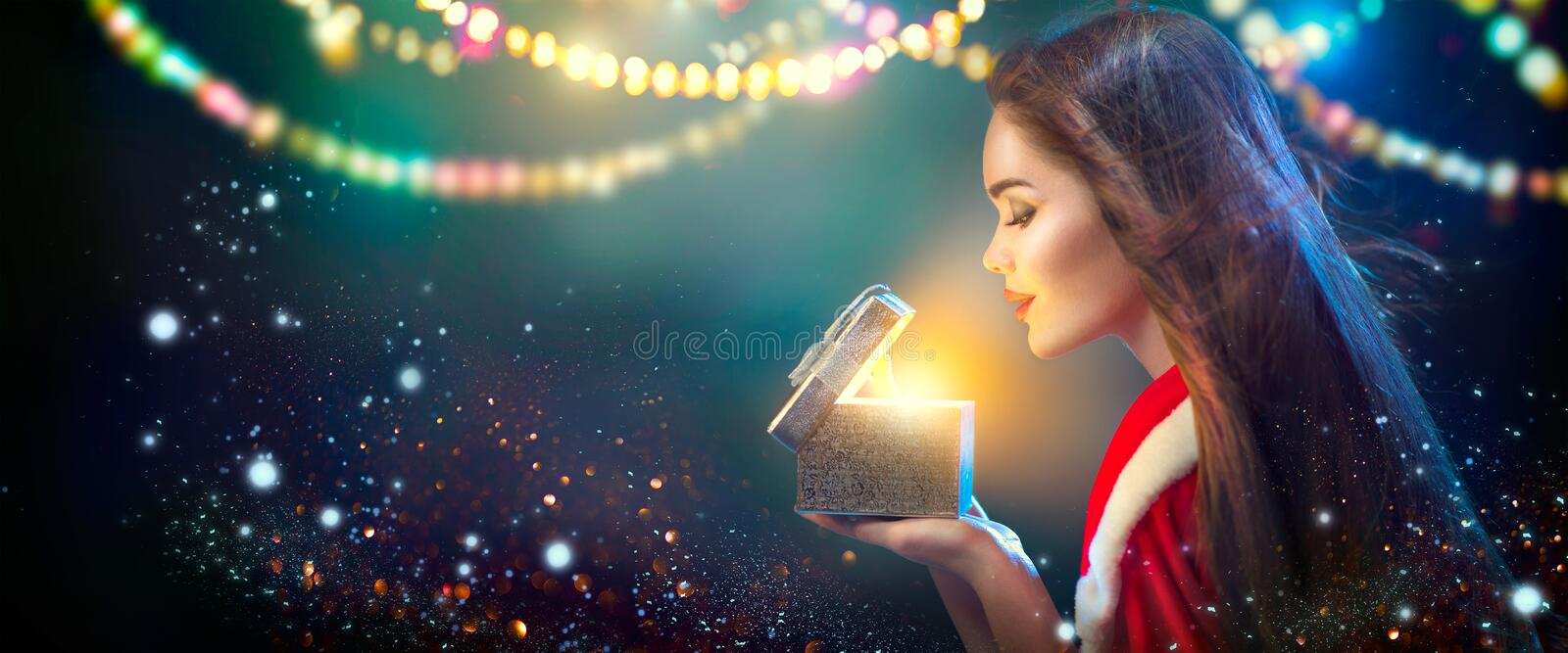 Christmas scene. Beauty brunette young woman in party costume opening gift box. Over holiday blurred background royalty free stock photo