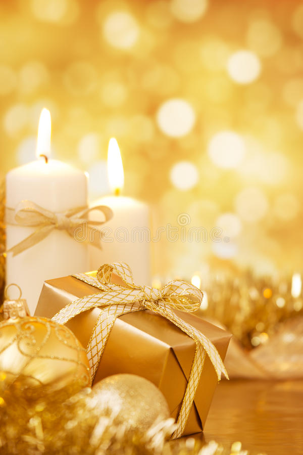 Christmas scene with gold baubles, gift and candles. Gold Christmas baubles, candles and a gift on a bright glittering gold background stock photo