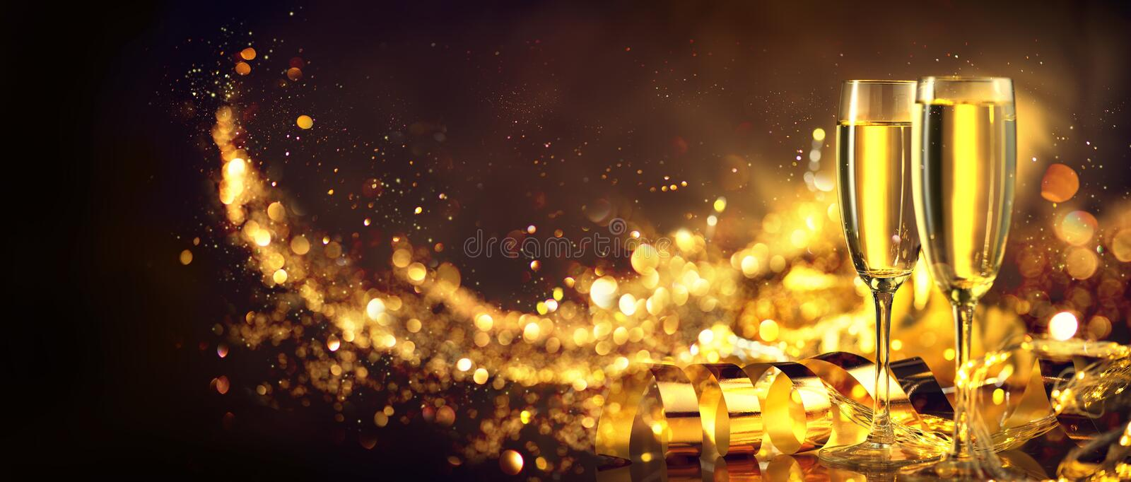 Christmas scene. Holiday champagne over golden glow background. Christmas and New Year celebration. Two flutes with sparkling wine royalty free stock photos