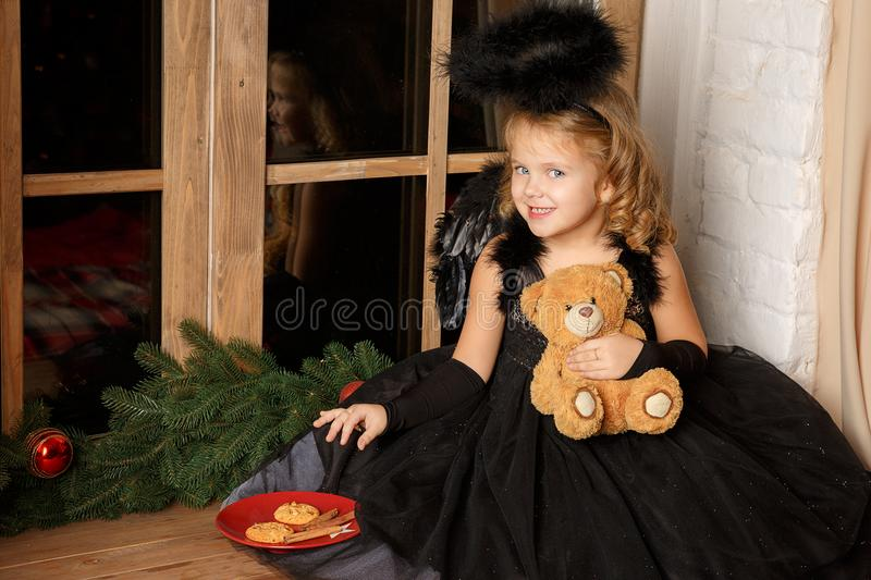 Christmas scene. portrait of a little blond girl, in a black angel costume stealing Santa`s cookies near the window. stock images