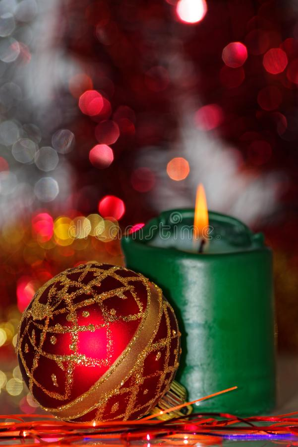 Red Christmas bauble and burning candle against blurred background royalty free stock image