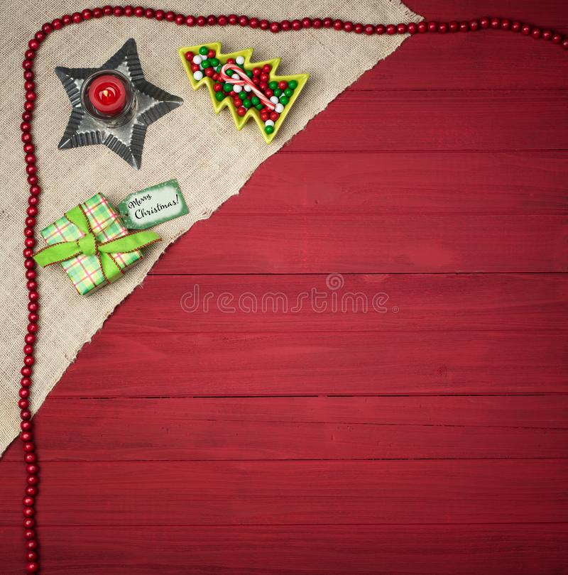 Christmas Scene with Rustic Red Boards Background and Tree Candy Dish, wrapped Present with Merry Christmas name tag.  It`s squar. E photo with flat layout and stock photos